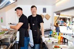 Die Gründer von Bunte Burger, Dr. Mario Binder und Ulrich Glemnitz, bei der Arbeit in ihrem Food Truck.